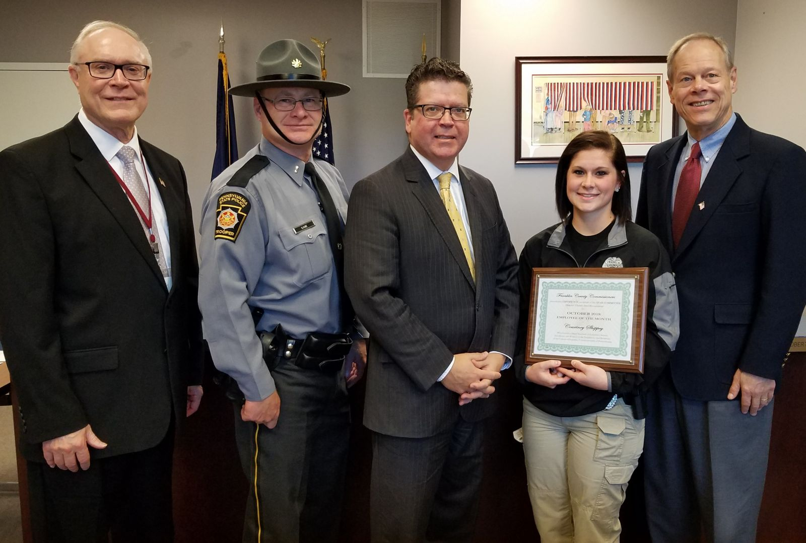 Pictured above (left to right): Commissioner Bob Thomas; Lieutenant Kane; Commissioner Chairman Dave Keller; Officer Courtney Shippey holding an award; Commissioner Bob Ziobrowski
