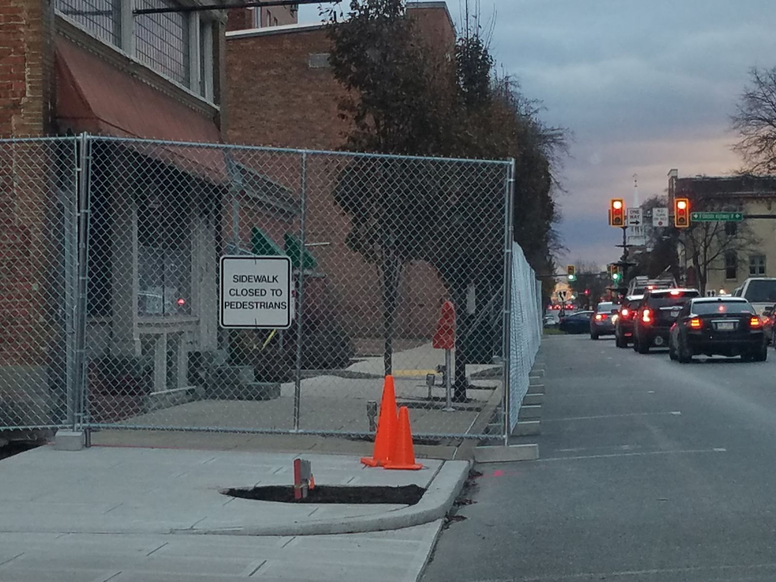 Sidewalk fencing along Main Street in Chambersburg with closed to pedestrian traffic sign.